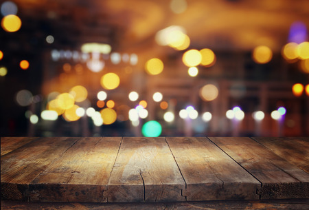 Foto de Image of wooden table in front of abstract blurred restaurant lights background - Imagen libre de derechos