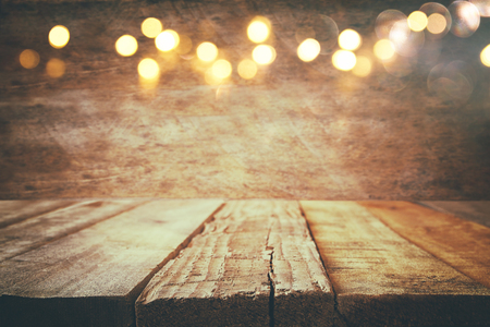 Photo pour empty table in front of Christmas warm gold garland lights on wooden rustic background. selective focus - image libre de droit