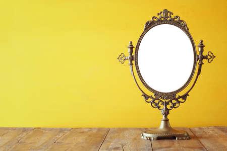 Foto de Old vintage oval mirror standing on wooden table. - Imagen libre de derechos
