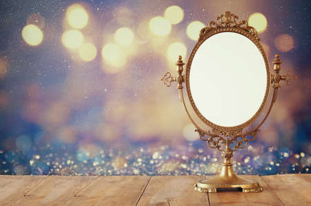 Foto de Old vintage oval mirror standing on wooden table. - Imagen libre de derechos
