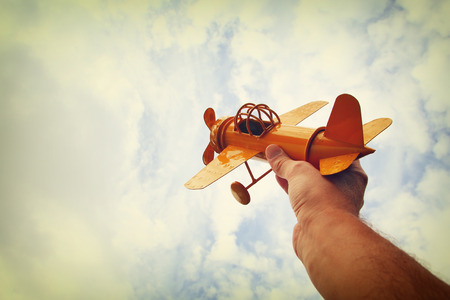 Photo pour close up photo of man's hand holding retro airplane against blue sky. Filtered image - image libre de droit