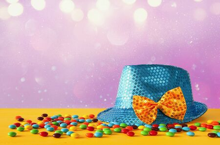 Photo for Blue shiny party Hat next to colorful candies on yellow wooden table - Royalty Free Image