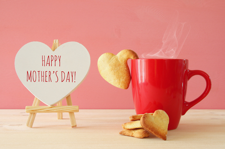 Photo for mother's day concept image. Board next to cup of coffee and heart cookies - Royalty Free Image