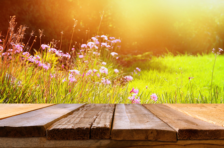 Foto de Empty rustic table in front of spring beautiful field flowers. product display and picnic concept - Imagen libre de derechos