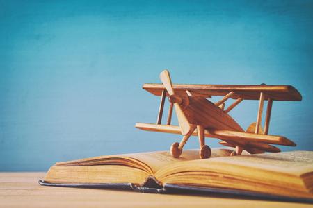 Photo pour Toy plane and the open book on wooden table. - image libre de droit