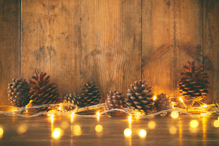 Photo for Holiday image with Christmas golden garland lights and pine cones over wooden background. - Royalty Free Image