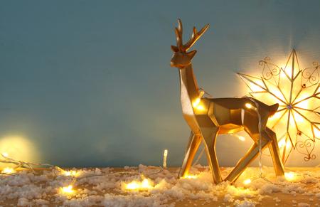 Foto de Gold shiny reindeer on snowy wooden table with christmas garland lights - Imagen libre de derechos
