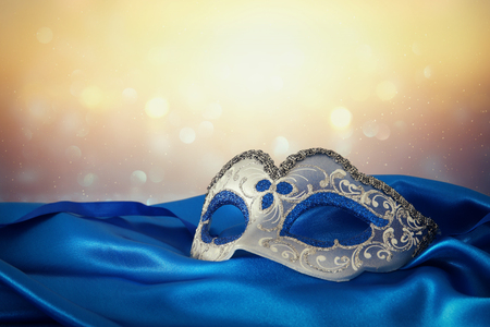 Photo for Image of elegant blue and gold venetian mask over blue silk fabric background - Royalty Free Image