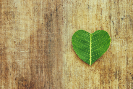 Photo for heart shaped leaf over wooden table. ecology and health concept - Royalty Free Image