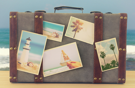 Photo for Image of old vintage luggage with vacation photos over wooden floor - Royalty Free Image