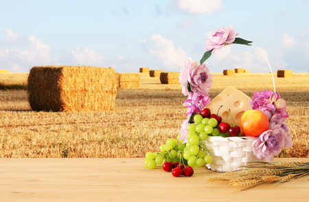 Foto de image of fruits and cheese in decorative basket with flowers over wooden table. Symbols of jewish holiday - Shavuot - Imagen libre de derechos