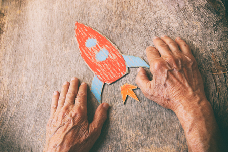 Foto de A close up of an elderly man holding a paper rocket on a wooden table. Concept of thinking about childhood dreams, sadness and loneliness. - Imagen libre de derechos