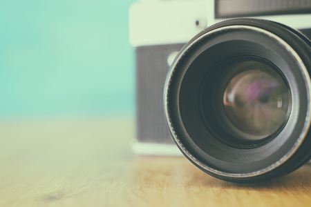 Photo pour old photo camera over white wooden desk. Vintage filtered - image libre de droit