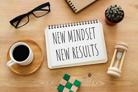 Foto de Top view image of table with open notebook and the text new mindset new results. Success and personal development concept - Imagen libre de derechos