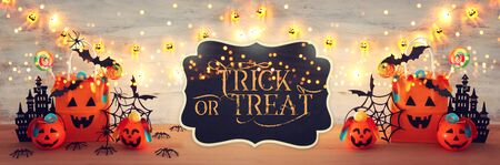 Photo pour holidays image of Halloween. Pumpkins, bats, treats, paper gift bag over wooden table - image libre de droit