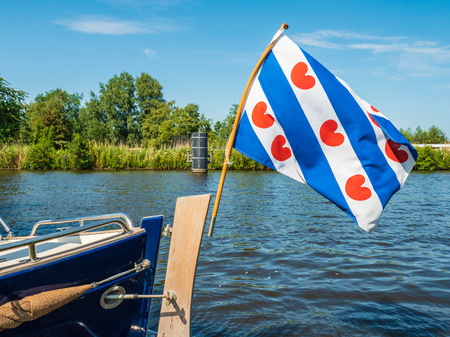 Foto de The Frisian flag waves proudly in the wind on the back of a motor sloop in the Dutch province of Friesland - Imagen libre de derechos
