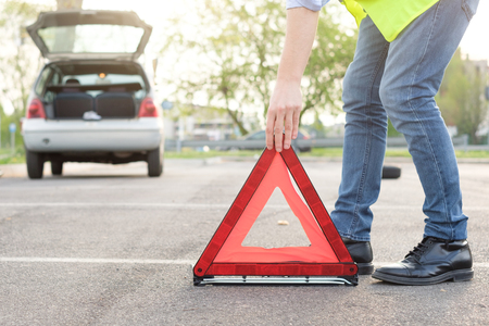 Photo for Man placing a reflective red triangle after car breakdown - Royalty Free Image