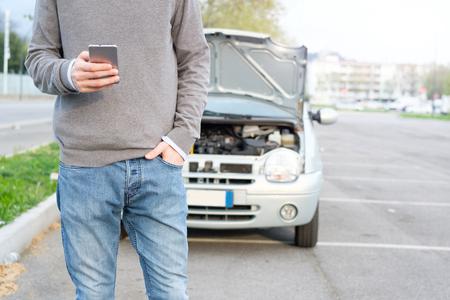 Foto de Man calling mechanic help service after car engine breakdown - Imagen libre de derechos