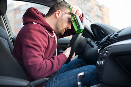 Photo pour Drunk man driving car and falling asleep at the wheel - image libre de droit