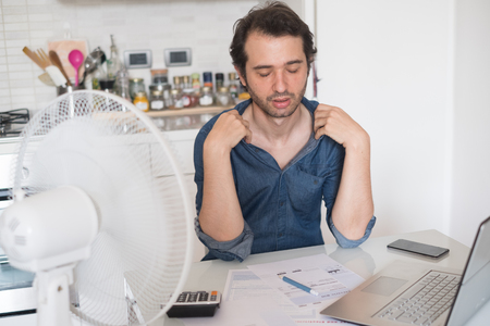 Photo for Sweaty man trying to refresh from heat with a fan - Royalty Free Image