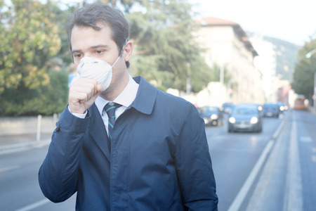 Photo pour Man walking in the city wearing protection mask against smog air pollution - image libre de droit