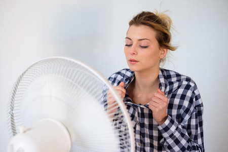 Photo pour Girl face expression cooling in front of a fan - image libre de droit