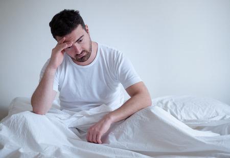Foto de Sad and upset man waking up in the morning light - Imagen libre de derechos
