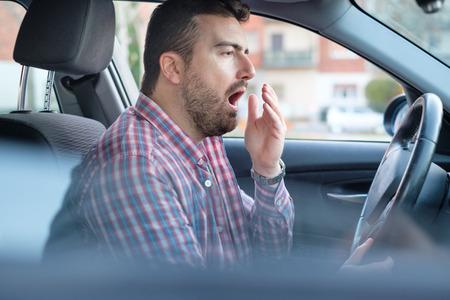 Foto de Bored and tired yawning man driving his car need a rest - Imagen libre de derechos