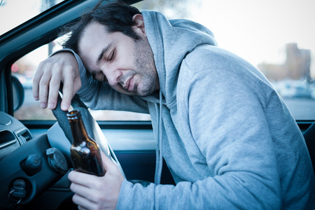 Photo pour Young man driving his car while drinking alcohol and falling asleep , blue effect added to increase drama - image libre de droit