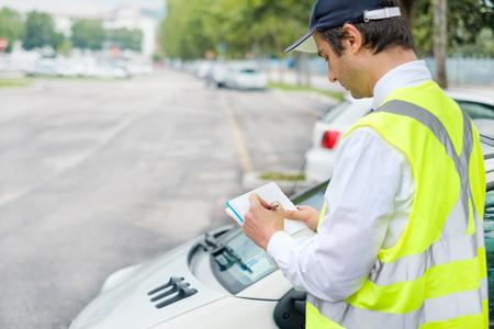 Foto de Parking officer writing a ticket for a parking violation - Imagen libre de derechos