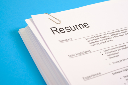 Photo for Stack of cv and application for employment on blue desk - Royalty Free Image