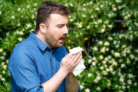 Photo pour Adult caucasian man sneezes because of an allergy. - image libre de droit