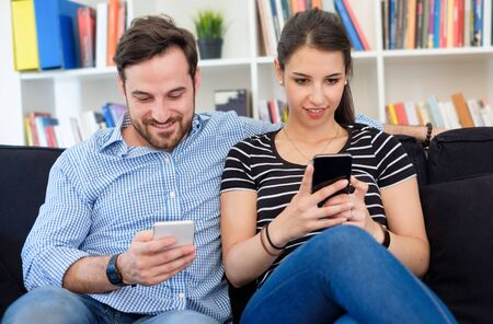 Photo pour Young couple using smartphone and relaxing at home - image libre de droit