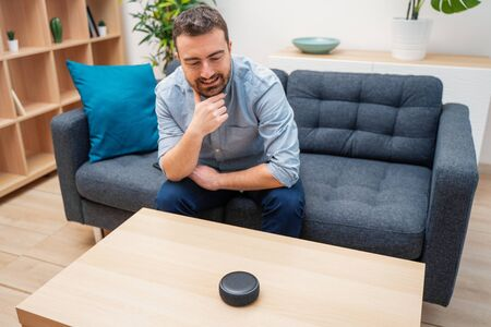 Foto de Man using virtual assistant and smart speaker at home - Imagen libre de derechos