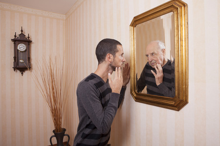 Photo pour young man looking at an older himself in the mirror - image libre de droit