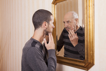 Foto de young man looking at an older himself in the mirror - Imagen libre de derechos