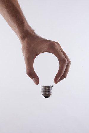 Photo pour abstract conceptual image of a male's hand holding a light bulb shape - image libre de droit