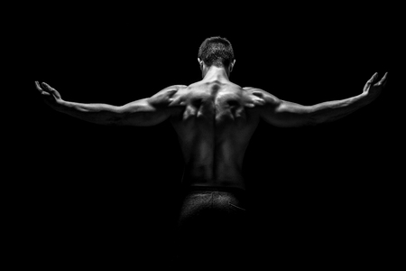 Foto de Rear view of healthy muscular young man with his arms stretched out on black background. Black and white - Imagen libre de derechos