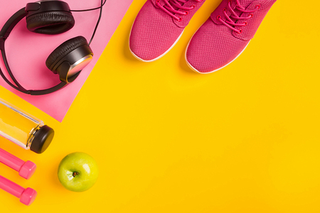 Fitness accessories on a yellow background. Sneakers, bottle of water, earphones and dumbbells. Still life