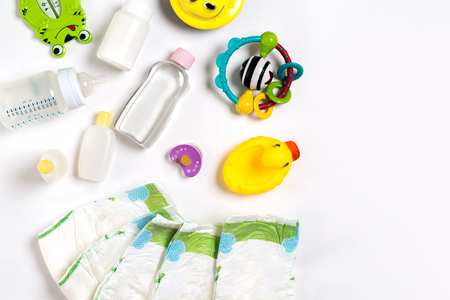 Photo pour Babies goods diaper, baby powder, cream, shampoo, oil on white background with copy space. Top view or flat lay. Maternity concept - image libre de droit