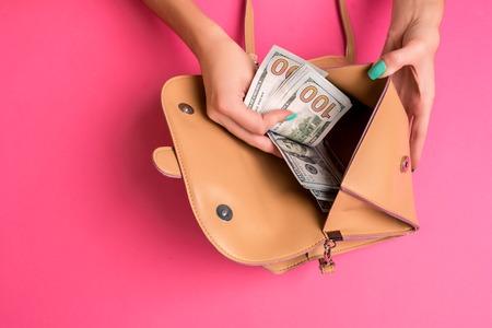Foto de Womans hand removing money from little bag, studio shot - Imagen libre de derechos