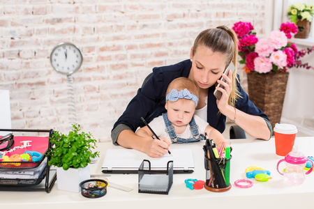 Foto de Family Business - telecommute Businesswoman and mother with kid is making a phone call - Imagen libre de derechos