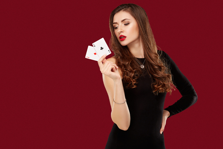 Foto de Beautiful caucasian woman in black dress with poker cards gambling in casino - Imagen libre de derechos