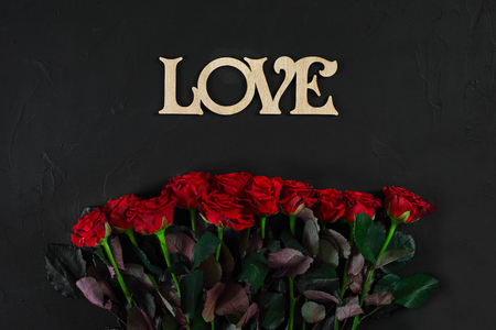 Red roses flowers with wooden word LOVE on black background with