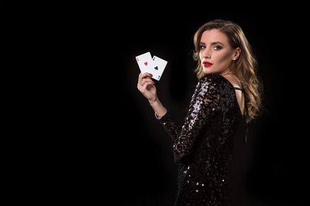 Photo pour Young woman holding playing cards against a black background - image libre de droit