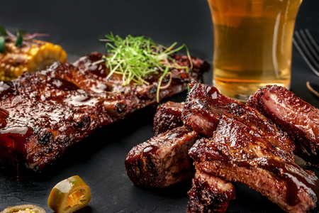 Photo for Pork ribs in barbecue sauce and a glass of beer on a black slate dish. A great snack to beer on a dark stone background. Top view with copy space - Royalty Free Image