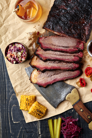 Photo pour Fresh Brisket BBQ beef sliced for serving against a kraft paper background with sauce, hot peppers and corn. Generous accommodation for copy space. American style - image libre de droit