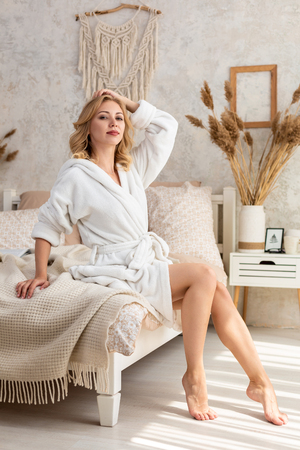 Photo for Awakened woman sitting on the edge of the bed looking out the window, bare feet on the floor. Side view of beautiful female legs. - Royalty Free Image