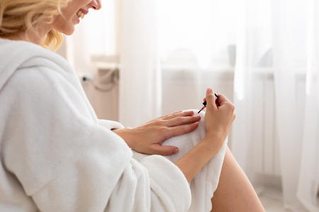 Photo for Close up of a shapely woman painted her nails in the morning, while sitting on the bed being dressed in a dressing-gown. - Royalty Free Image