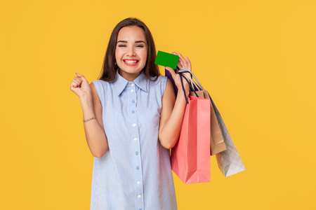 Foto für Trendy woman 20s in dress with long brown hair smiling while holding different shopping packages and card in hands isolated over yellow background - Lizenzfreies Bild